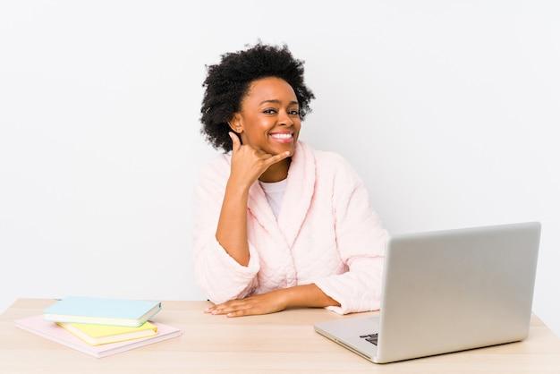 Afro-amerikaanse vrouw van middelbare leeftijd werken thuis geïsoleerd met een gebaar van de mobiele telefoongesprek met vingers.