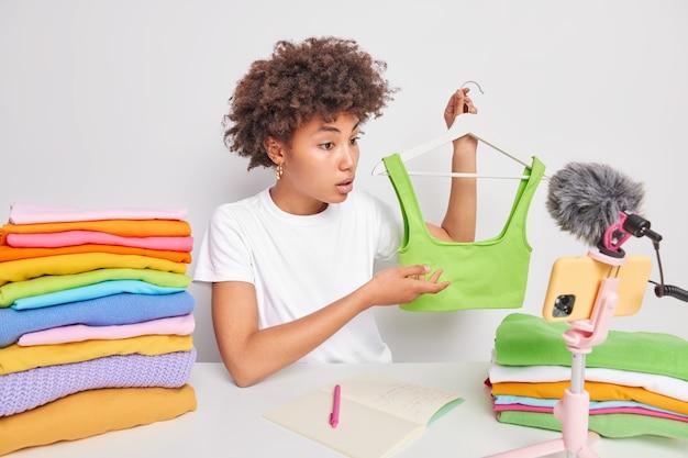 Afro-amerikaanse vrouw verkoopt kleding via live-uitzending via internetkanaal houdt groene top op hanger records beoordeling van nieuwe kledingcollectie maakt merkpromo adverteert modieuze trends