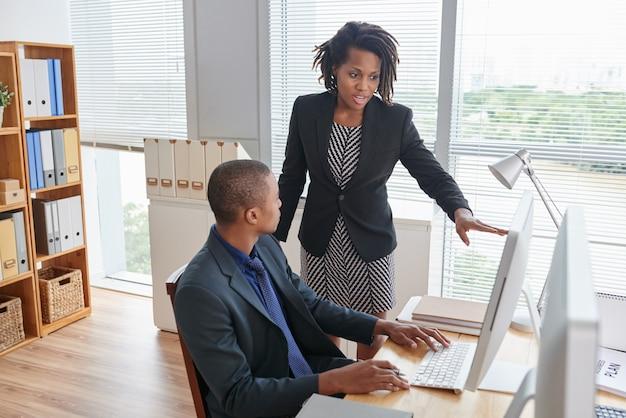 Afro-amerikaanse vrouw wijst naar computerscherm en praat met junior mannelijke collega