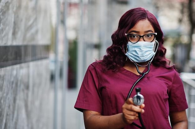 Afro-amerikaanse vrouwelijke arts op rode lab uniform in beschermend gezichtsmasker. geneeskunde, beroep en gezondheidszorg concept. stop de coronavirus-infectie.