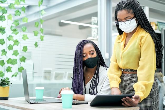 Afro-amerikaanse vrouwelijke collega's praten over samenwerken in kantoorvergadering