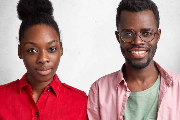 Afro-amerikaanse vrouwelijke en mannelijke klasgenoten ontmoeten elkaar na lange tijd, wisselen nieuws uit, staan dicht bij elkaar.