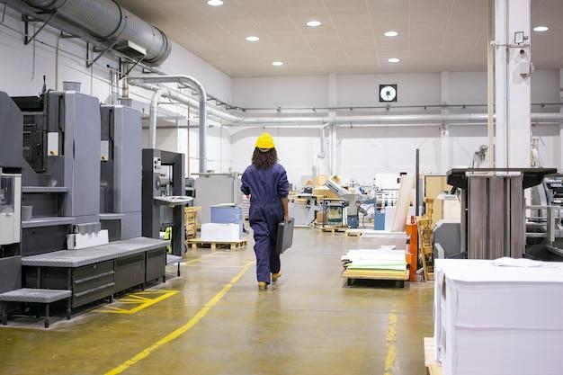 Afro-amerikaanse vrouwelijke industriële werknemer in veiligheidshelm en over het algemeen lopen op de fabrieksvloer