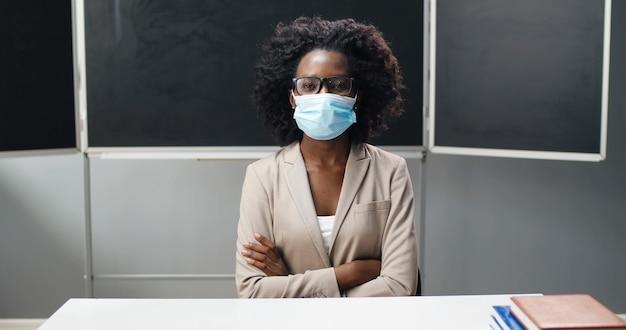 Afro-amerikaanse vrouwelijke leraar in glazen en medische masker zittend aan tafel op school in de klas, leerboek lezen en lesgeven. literatuurles. vrouw opvoeder vragen van studenten of leerlingen