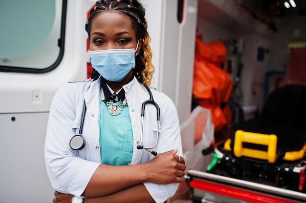 Afro-amerikaanse vrouwelijke paramedicus in gezichtsmasker staande voor ambulance auto