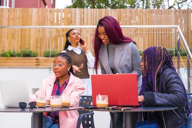 Afro-amerikaanse vrouwen op een zakelijke bijeenkomst in een cafetaria met laptops en koffie op tafel