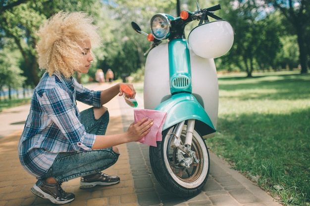 Afro-amerikaanse vrouwen wassen scooter. meisje schoonmaken de blauwe bromfiets of motorfiets.