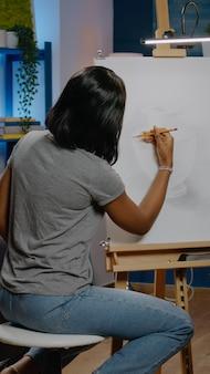 Afro-amerikaanse vrouwenkunstenaar die vaasontwerp maakt met potlood