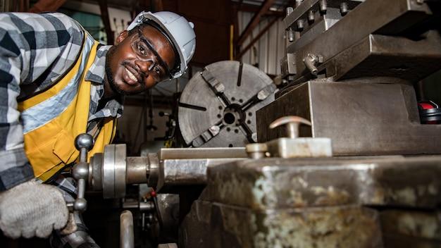 Afro-amerikaanse werknemer die een veiligheidsbril draagt, bestuurt de draaibankmachine om componenten met een sleutel te boren;