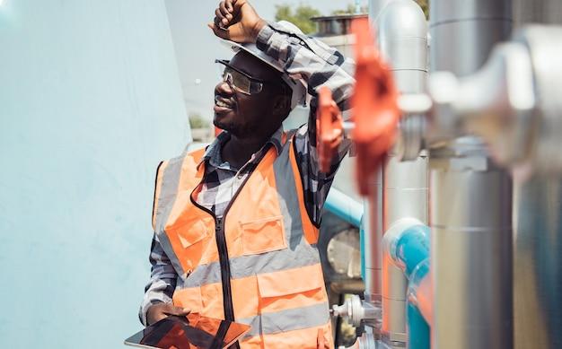 Afro-amerikaanse werknemer die een veiligheidsbril draagt met zijn arm omhoog op zijn harde veiligheidshelm