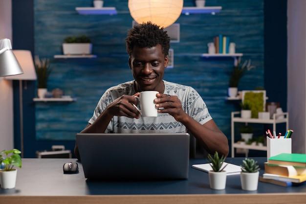 Afro-amerikaanse zakenman die een kopje koffie vasthoudt en managementideeën typt