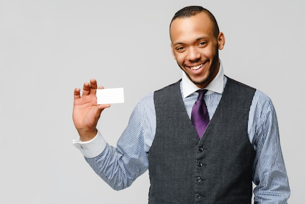 Afro-amerikaanse zakenman die een wit leeg adreskaartje houdt.