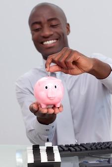Afro-amerikaanse zakenman die geld in een piggybank bespaart