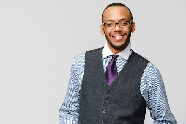 Afro-amerikaanse zakenman die glazenportret over grijze muur draagt