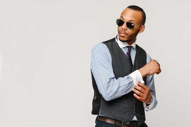 Afro-amerikaanse zakenman die glazenportret over grijze muur draagt.