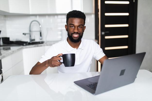 Afro-amerikaanse zakenman drinkt koffie, kijkt naar de camera en lacht terwijl hij in de keuken staat