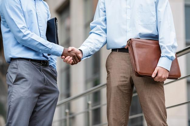 Afro-amerikaanse zakenman en een blanke zakenman handen schudden op de gebouwen, close-up