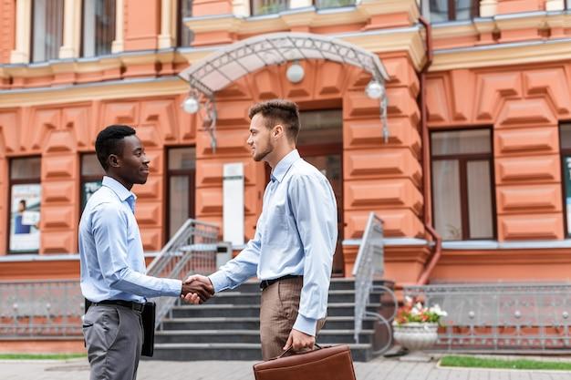 Afro-amerikaanse zakenman en een blanke zakenman handen schudden op de rode gebouwen in de stad