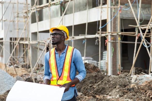 Afro-amerikaanse zakenman in beschermende veiligheid harde hoed blauwdruk plannen op bouwplaats kijken.