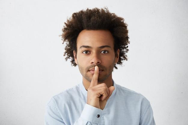 Afro amerikaanse zakenman in formele slijtage wijsvinger op zijn lippen te houden