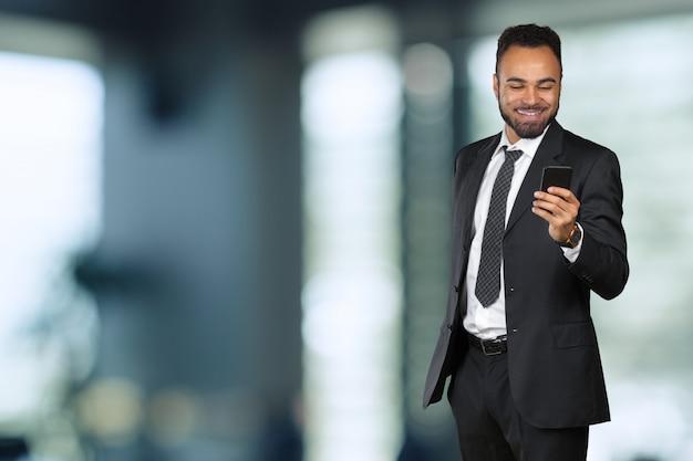 Afro-amerikaanse zakenman met behulp van de mobiele telefoon