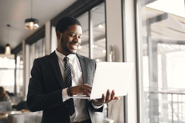 Afro-amerikaanse zakenman met behulp van een laptop in een café.