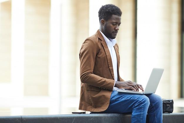 Afro-amerikaanse zakenman met behulp van laptop in stad