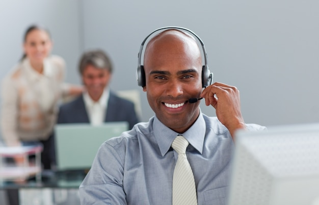 Afro-amerikaanse zakenman met hoofdtelefoon op werken op een computer