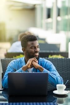 Afro-amerikaanse zakenman met laptop in een café