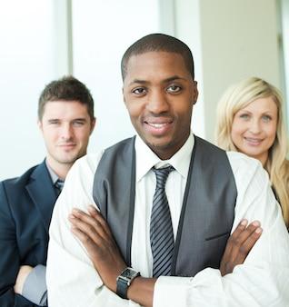 Afro-amerikaanse zakenman met zijn collega's die bij de camera glimlachen