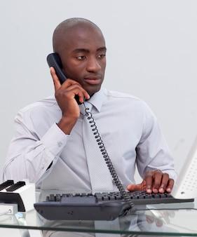 Afro-amerikaanse zakenman op telefoon in het kantoor
