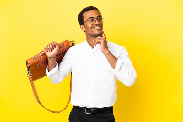 Afro-amerikaanse zakenman over geïsoleerde gele achtergrond die een idee denkt terwijl hij omhoog kijkt