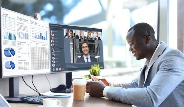 Afro-amerikaanse zakenman praat met zijn collega's in videoconferentie. multi-etnisch business team werkt vanuit kantoor met behulp van pc en bespreekt het financiële rapport van hun bedrijf.