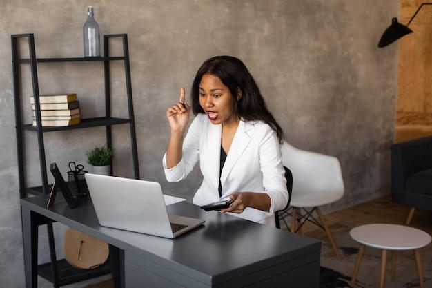 Afro-amerikaanse zakenvrouw als leider op het werk teamwerk en multi-etnisch concept gelukkig succesvolle zakelijke leider werkt op haar kantoor kijken en glimlachen in de camera