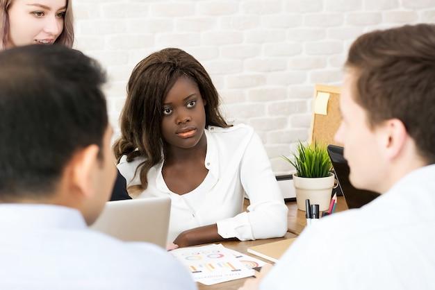 Afro-amerikaanse zakenvrouw baas concentreren en luisteren haar collega in de vergadering