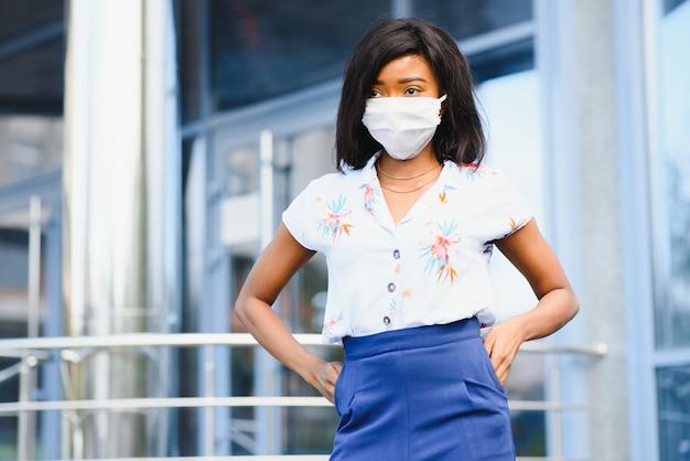 Afro-amerikaanse zakenvrouw beschermend masker dragen op haar gezicht in de stad