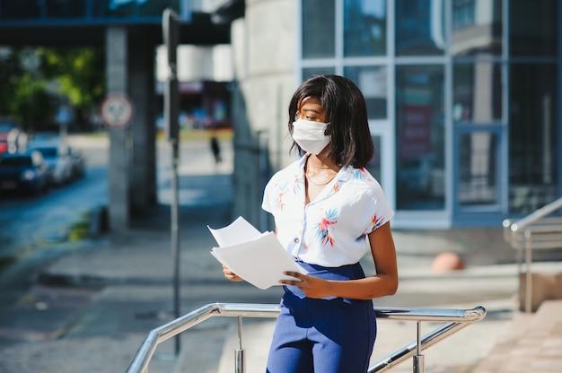 Afro-amerikaanse zakenvrouw beschermend masker dragen
