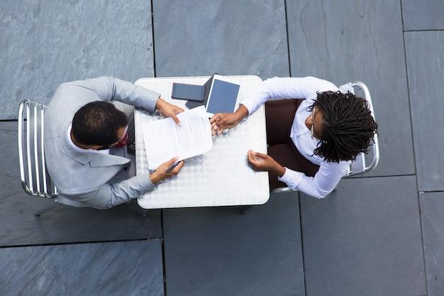 Afro-amerikaanse zakenvrouw documenten doorgeven aan collega