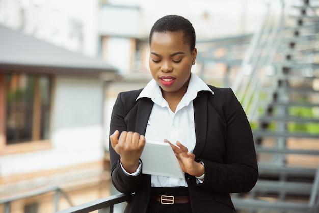 Afro-amerikaanse zakenvrouw in kantoor kleding lachend, ziet er zelfverzekerd en gelukkig, druk