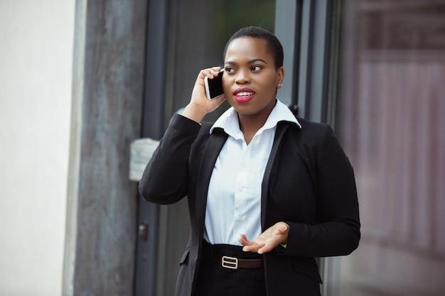Afro-amerikaanse zakenvrouw in kantoorkleding die lacht, ziet er zelfverzekerd uit als ze aan de telefoon praat