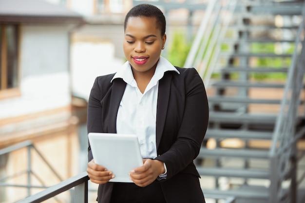 Afro-amerikaanse zakenvrouw in kantoorkleding met behulp van tablet