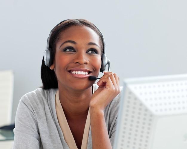 Afro-amerikaanse zakenvrouw met behulp van de hoofdtelefoon