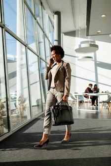 Afro-amerikaanse zakenvrouw met tas met behulp van mobiele telefoon en wandelen in het kantoor