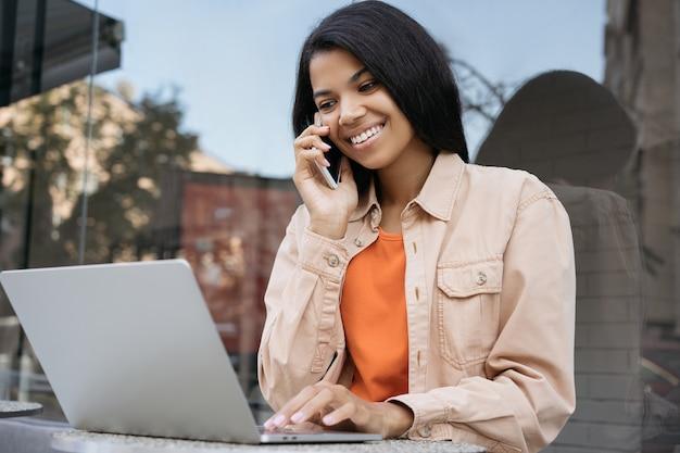 Afro-amerikaanse zakenvrouw online werken, met behulp van laptopcomputer, praten op mobiele telefoon zitten in café