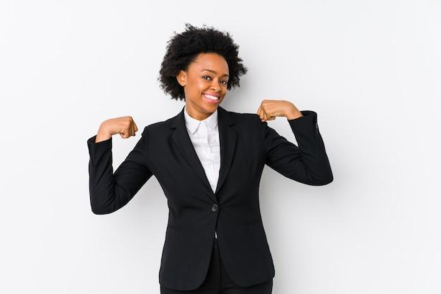 Afro-amerikaanse zakenvrouw van middelbare leeftijd tegen een geïsoleerd wit krachtgebaar met armen, symbool van vrouwelijke kracht