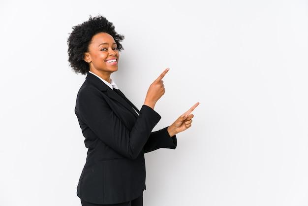 Afro-amerikaanse zakenvrouw van middelbare leeftijd tegen een wit geïsoleerd opgewonden wijzend met wijsvingers weg.