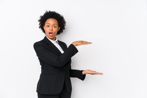 Afro-amerikaanse zakenvrouw van middelbare leeftijd tegen een witte achtergrond geïsoleerd geschokt en verbaasd met een kopie ruimte tussen handen.