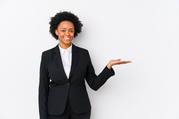 Afro-amerikaanse zakenvrouw van middelbare leeftijd tegen een witte achtergrond geïsoleerd met een kopie ruimte op een palm en met een andere hand op de taille.
