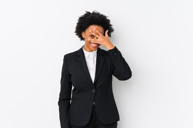 Afro-amerikaanse zakenvrouw van middelbare leeftijd tegen een witte muur geïsoleerd knipperen naar de camera door vingers, beschaamd bedekkend gezicht.