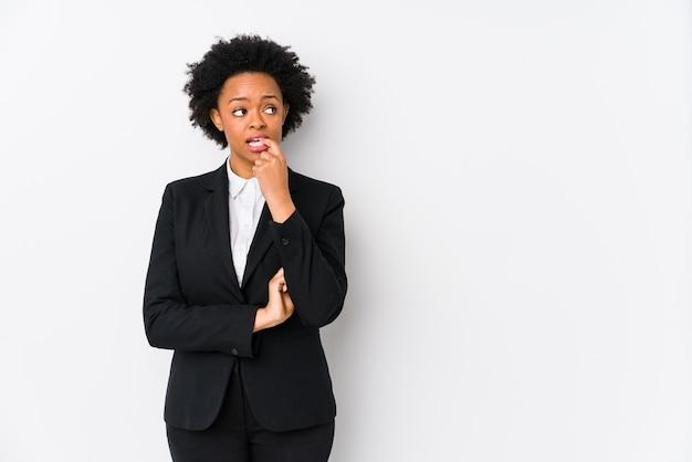 Afro-amerikaanse zakenvrouw van middelbare leeftijd tegen een witte muur geïsoleerd ontspannen denken aan iets kijken naar een kopie ruimte.